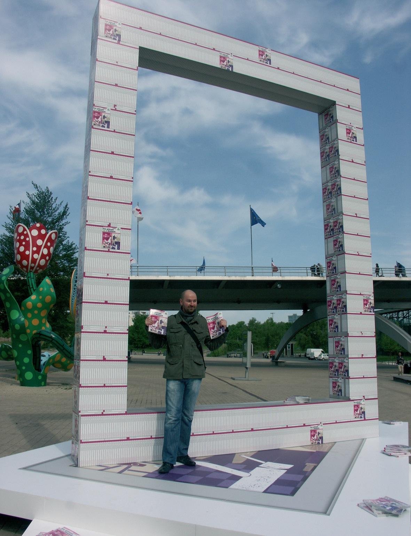 Christian Mairesse prend la pose devant l'arche de catalogues qui accompagne la distribution dans sept villes de France.