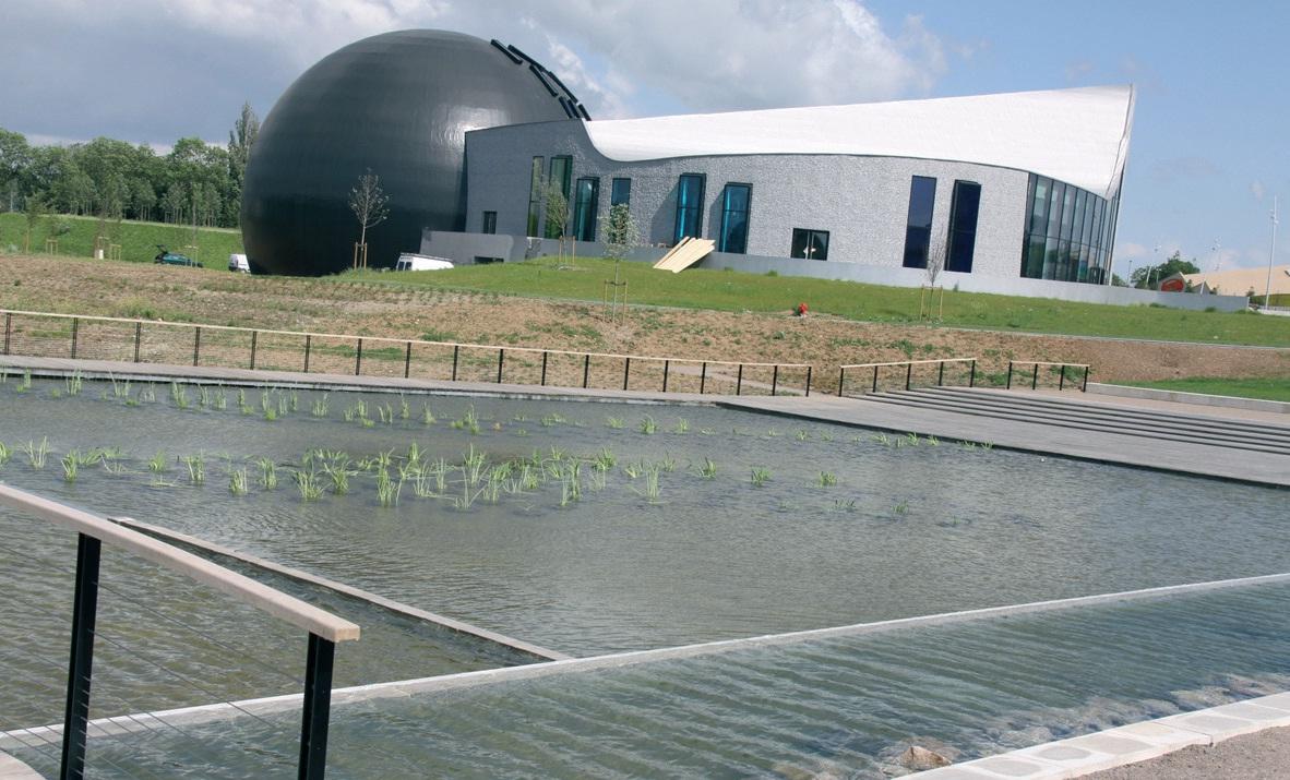 La vue sur Aquarena à partir des nouveaux bassins aquatiques permet de distinguer la ripisylve (formations végétales se développant sur les bords des cours d'eau ou des plans d'eau).