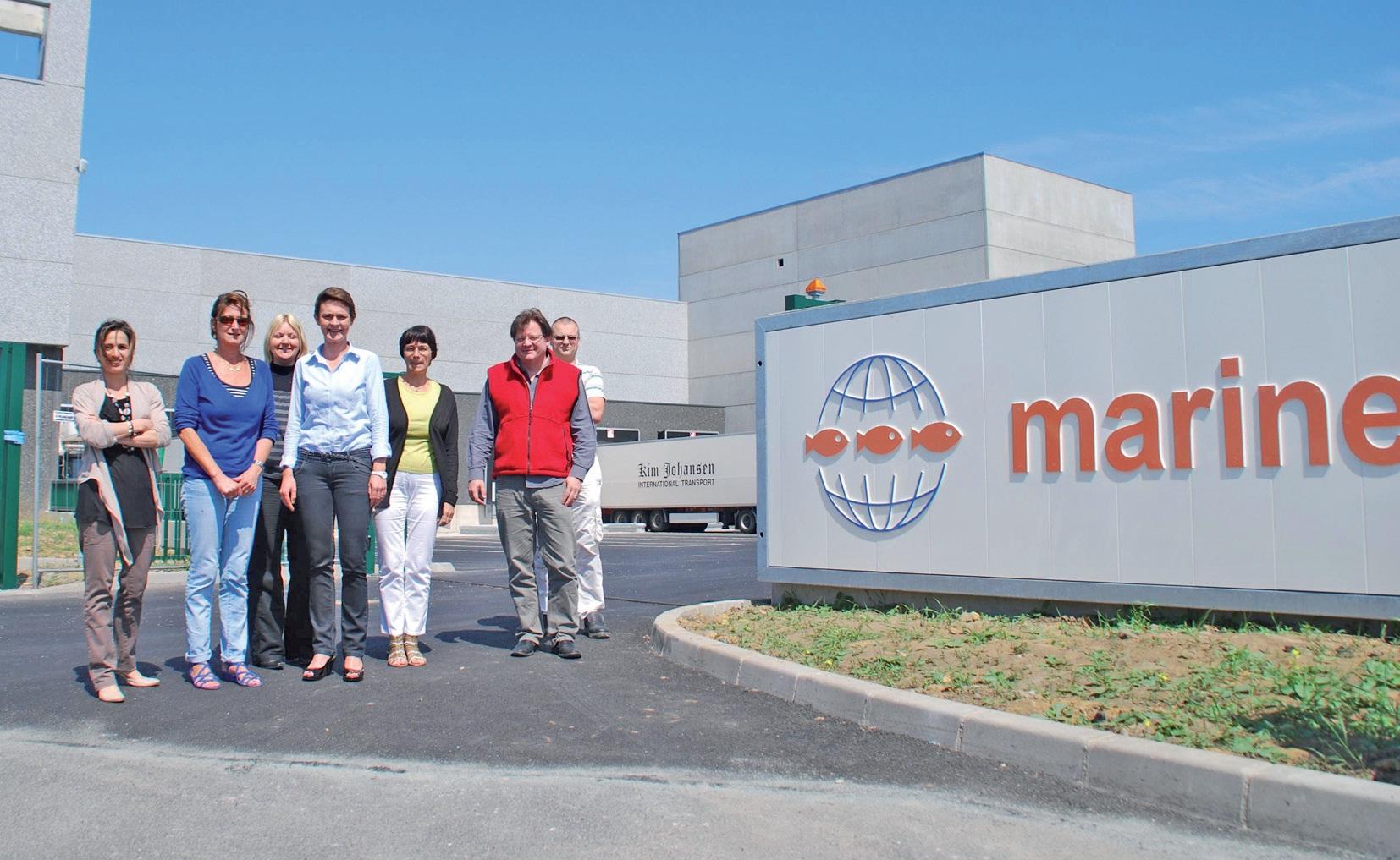 à l'entrée de la nouvelle usine, le directeur Jean Deterre (en gilet rouge), entouré de plusieurs de ses collaborateurs.