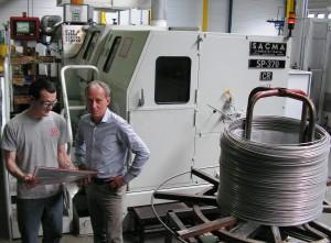 A côté de la presse transfert multiposte (déformation à froid, découpe, contrôle…) alimentée par des bobines de fils : Olivier Carnière, l'actuel dirigeant, et Mickaël Bouillon, régleur.