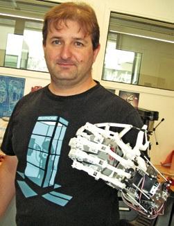 Nicolas Daddato avec un exosquelette de sa fabrication qui doit servir à un motard privé de l'usage normal de son bras.